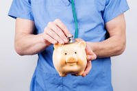 Doctor checking piggy bank with stethoscope