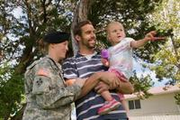 Military family with their daughter outside.