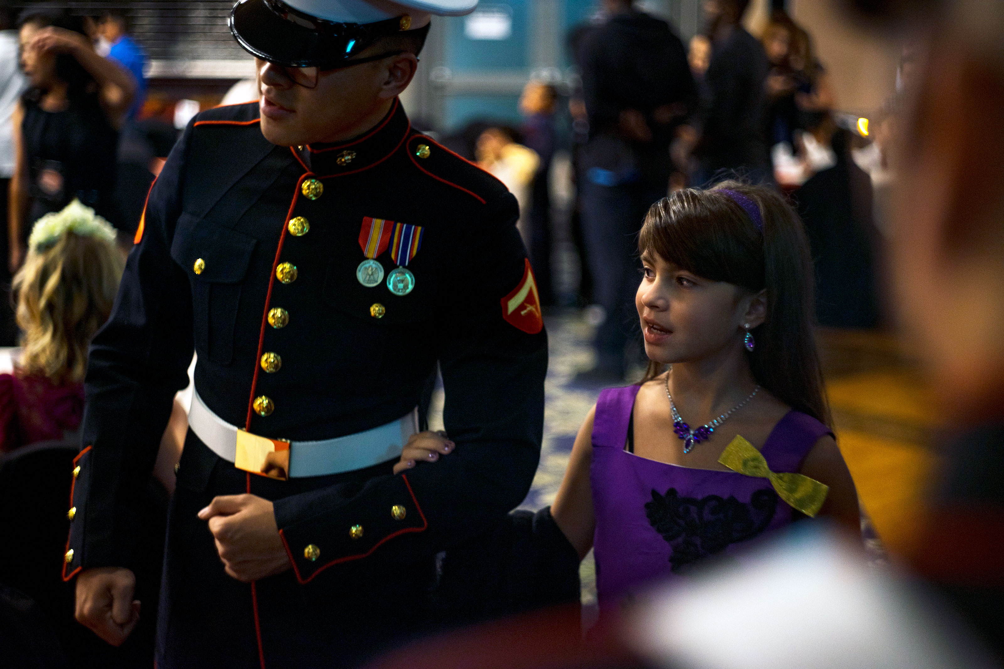 A U.S. Marine escorts a child to her seat during the Seventh Annual Mini Marine Corps and Navy Ball at Marine Corps Air Station Iwakuni, Japan, Oct. 21, 2017.  (U.S. Marine Corps/Donato Maffin)