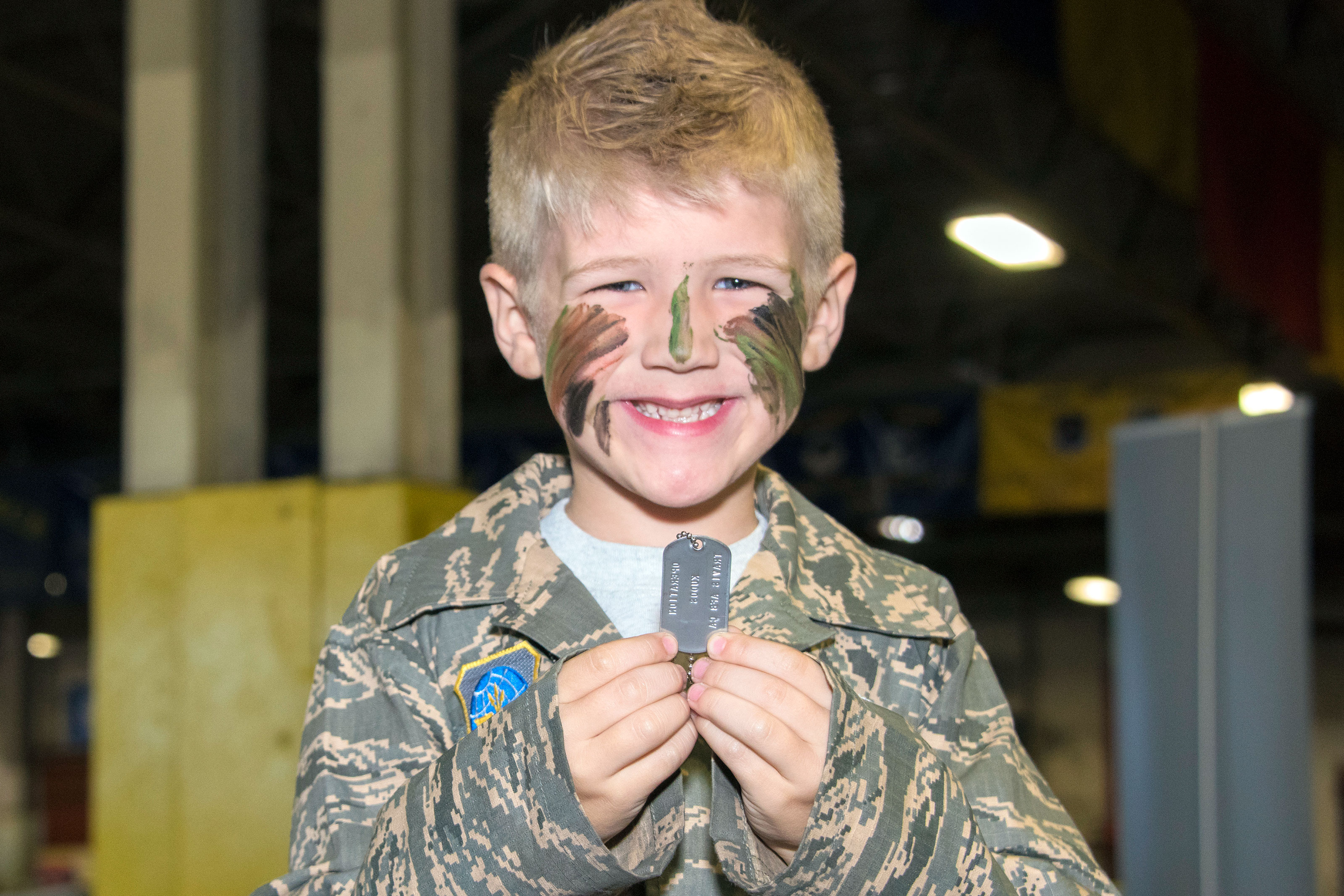 A child displays the dog tags he received as part the out-processing line at the 60th Aerial Port Squadron cargo warehouse, set up to host U. S. Air Force families for Kids Understanding Deployment Operations day, Oct. 21, 2017, Travis Air Force Base Calif. (U.S. Air Force/Heide Couch)