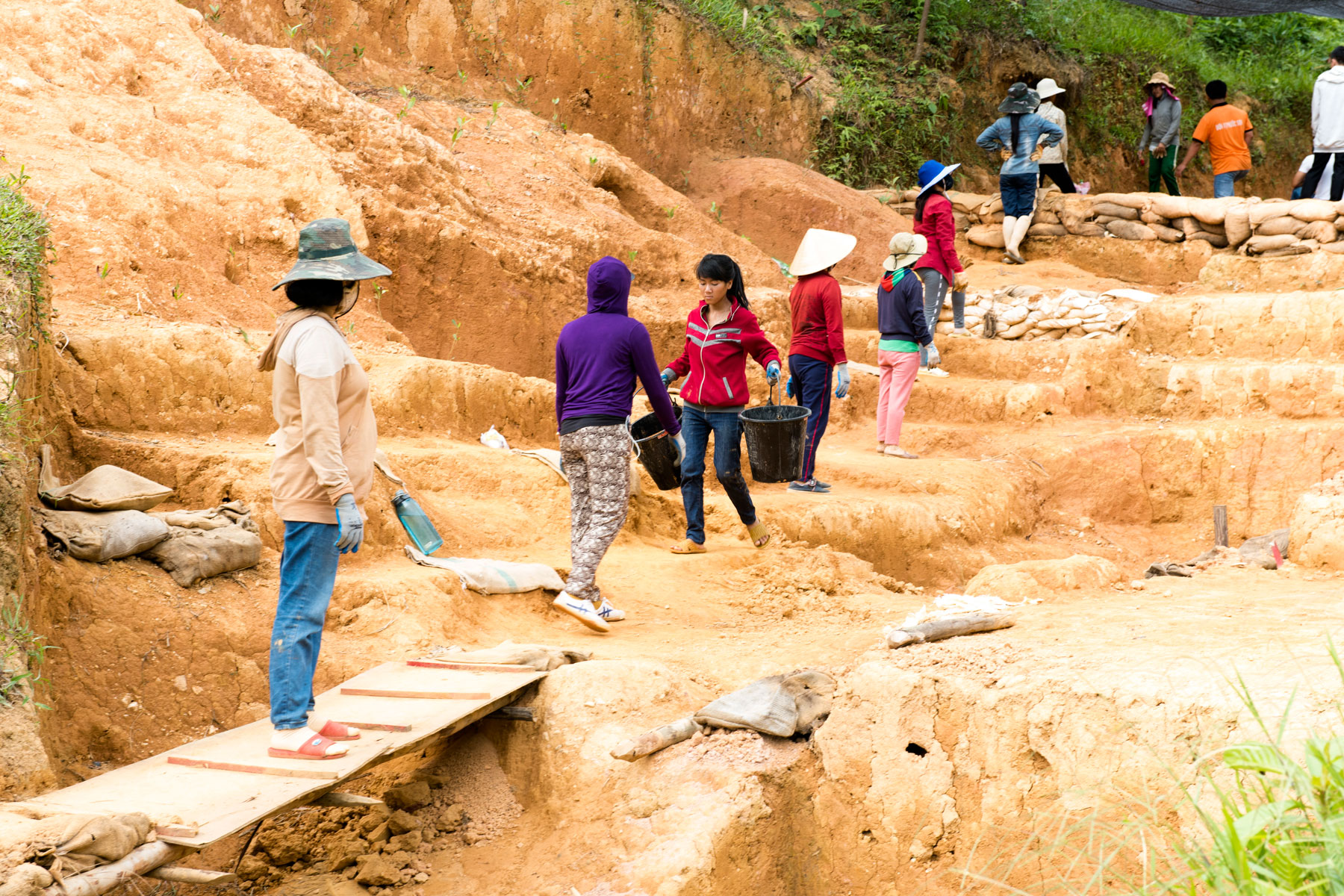 Local workers assisting a Defense POW/MIA Accounting Agency (DPAA) recovery team pass buckets of excavated soil during operations in Quang Nam province, Socialist Republic of Vietnam, June 18, 2018. A DPAA recovery team deployed to the area in search of the remains of U.S. service members lost during the Vietnam War. (U.S. Navy photo by Mass Communication Specialist 2nd Class Claire Farin)