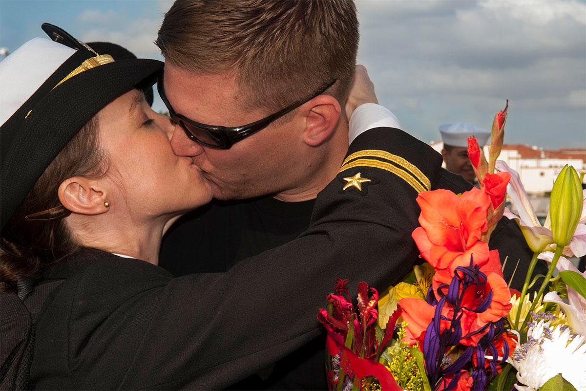 Lt. Katie Jacobson greets her husband Lt. Kevin Jacobson with a kiss