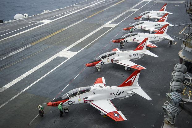 Pilots perform pre-flight procedures in T-45C Goshawks from Training Air Wing One 1 on the flight deck of the aircraft carrier USS George Washington on Dec. 10, 2016. The wing's Training Squadron 7 is on a stand-down after a crash that killed two. Petty Officer 2nd Class Bryan Mai/Navy