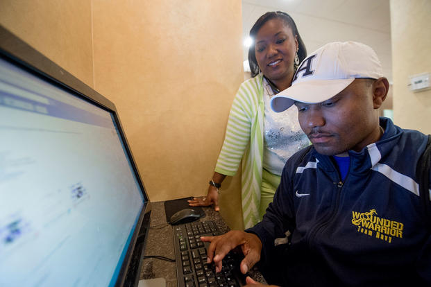 Ida Malone watches her husband, Navy Chief Petty Officer Averill Malone, as he checks for job offers in his email. Ida is also Averill's caregiver who helps prevent him reacting to situations that could trigger his post-traumatic stress disorder. (Defense Department/EJ Hersom)