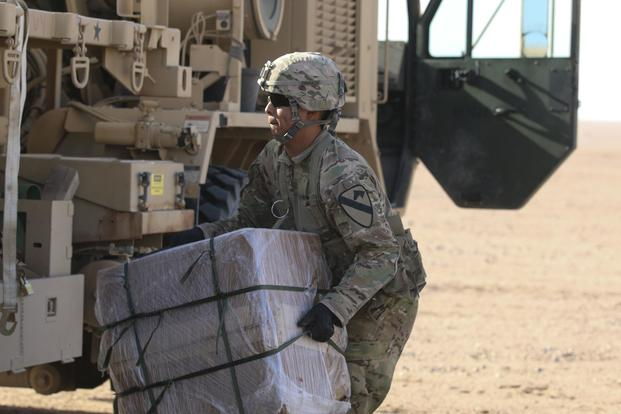 A soldier assigned to 215th Brigade Support Battalion, 3rd Armored Brigade Combat Team, 1st Cavalry Division, recovers a bundle off a drop zone during air drop resupply training July 27, 2017, at Udairi Range Complex, Kuwait. Staff Sgt. Leah R. Kilpatrick/Army