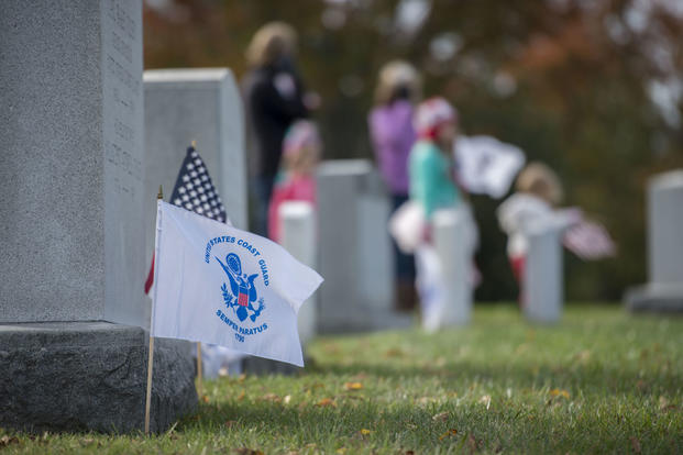 A Coast Guard and National Ensign mark a grave of a fallen Coast Guardsman during an annual Flags Across America event at Arlington National Cemetery, Nov. 4, 2017. (Coast Guard photo/Petty Officer 2nd Class Loumania Stewart)