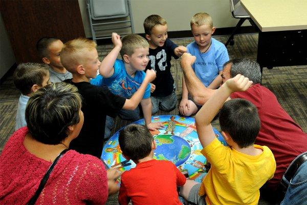 "Children of military families celebrate after completing a puzzle during ""Kids Chat"", a service provided by the Army's family advocacy program at Fort Carson, Colo. (US Army photo/Nathan Thome)"