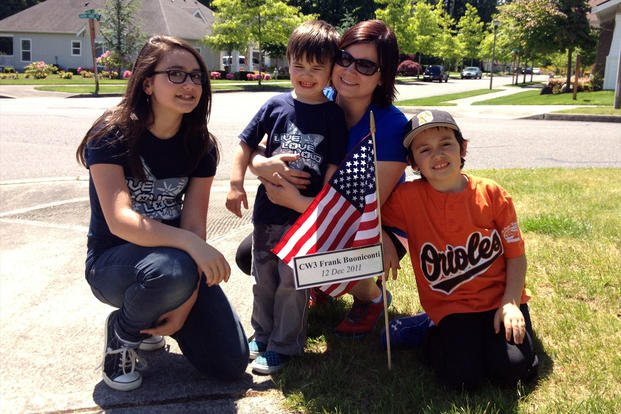 Kryste Buoniconti and her children pose with a sign and flag honoring her husband, Frank. (Courtesy of Kryste Buoniconti)