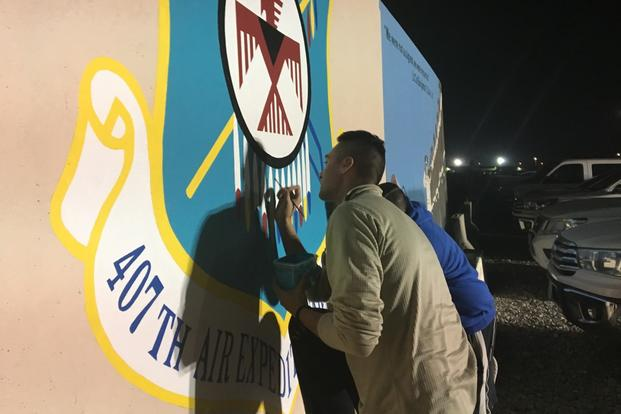 Staff Sgt. Shane Materkowski, foreground, works on a group mural in late December 2017 at a base in Southwest Asia. (Photo by Hope Hodge Seck/Military.com)