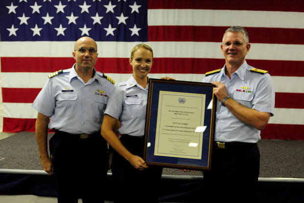 Coast Guard Petty Officer 2nd Class Sara Faulkner, receives recognition from Rear Admiral Bill Baumgartner, Commander of the 7th Coast Guard District and Capt. John Turner, commanding officer of Air Station Clearwater during an awards ceremony at Air Station Clearwater. (U.S. Coast Guard/Tara Molle)