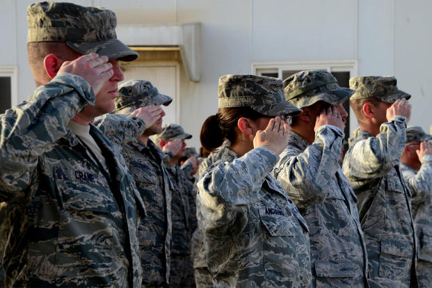 Airmen from the 379th Expeditionary Maintenance Group salute the U.S. flag during a ceremony at Al Udeid Air Base, Qatar. Members of the unit reported sickness caused by mold on the base. (US Air Force photo/Kia Atkins)