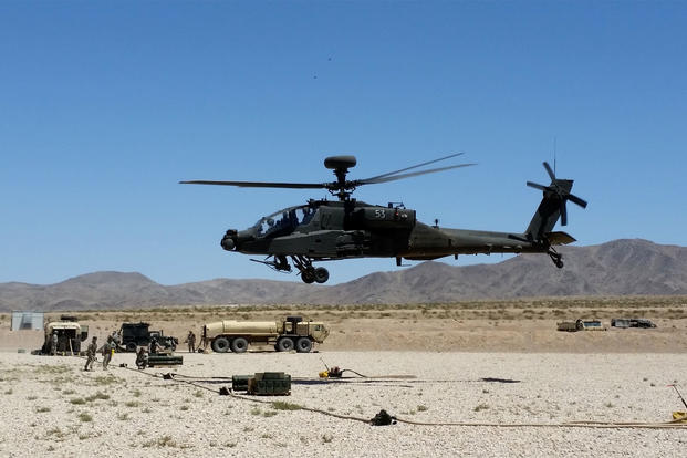 An AH-64E Apache helicopter takes off from its landing pad after arming and refueling during a rotation at the National Training Center in Fort Irwin, Calif. (US Army photo/Andrew Ruiz)
