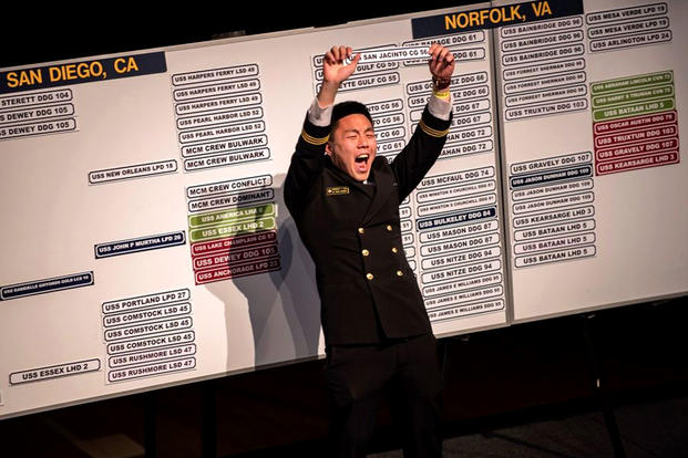 Midshipman First Class Andrew J. Ahn holds up a sign for the USS San Jacinto during Ship Selection Night at the U.S. Naval Academy on Jan 25. (US Navy photo/Kaitlin Rowell)