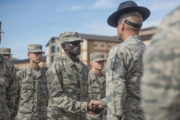 "Gour Maker, a trainee at basic military training, receives an ""Airman's Coin"" at the Coin Ceremony Feb. 1, 2018 outside the Pfingston Reception Center at Joint Base San Antonio-Lackland, Texas. Maker was recognized by his wingmen as a selfless leader and motivator during his time at BMT. (U.S. Air Force/Dillon Parker)"