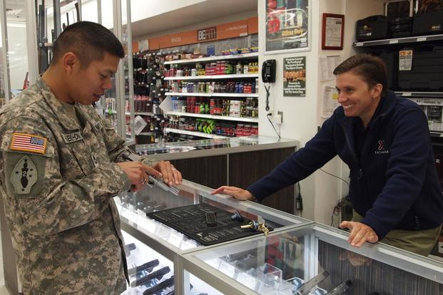 A Post Exchange gun sales supervisor shows a solider an American Classic handgun at the PX gun counter at Fort Huachuca. (U.S. Army Gabrielle Kuholski)