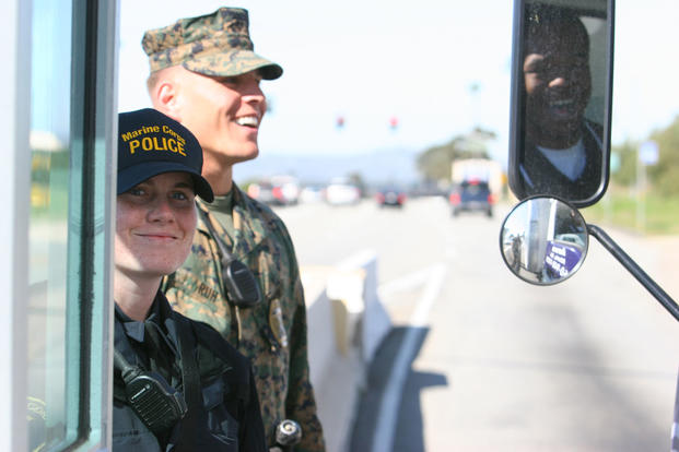 A military police officer, right, works alongside recently hired civilian police officer, left, as they monitor traffic going in and out Camp Pendleton's front gate in 2009. (U.S. Marine Corps photo/Daniel Boothe)