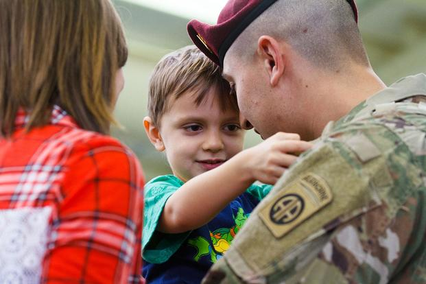 A paratrooper from the 1st Brigade Combat Team, 82nd Airborne Division, hugs his family after returning home on Feb. 14, 2018, at Fort Bragg, N.C. Gin-Sophie DeBellotte/Army