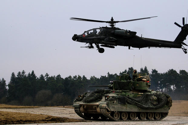 An M2 Bradley fighting vehicle and an AH-64 Apache helicopter secure an area during a Combined Arms Live Fire Exercise (CALFEX) in Grafenwoehr Training Area, Germany in March 2018. (US Army photo/Hubert Delany III)