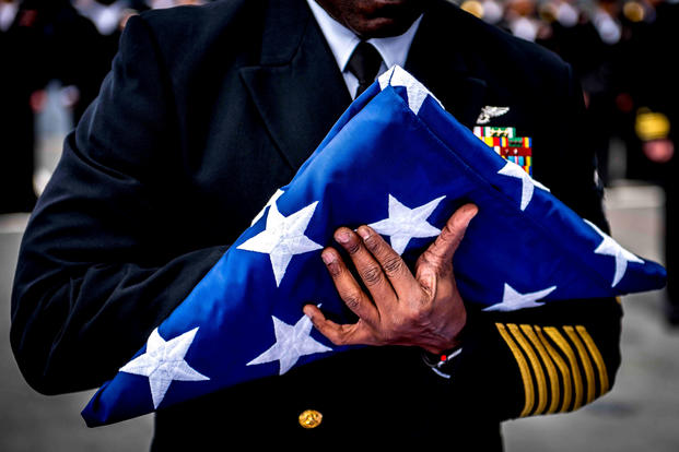 Command Master Chief Huben Phillips prepares to present the ensign during a burial-at-sea ceremony aboard the aircraft carrier USS George H.W. Bush (CVN 77). (U.S. Navy/Hank Gettys)