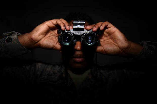 An airman looks through night vision goggles. (U.S. Air Force photo/Kevin Sommer Giron)