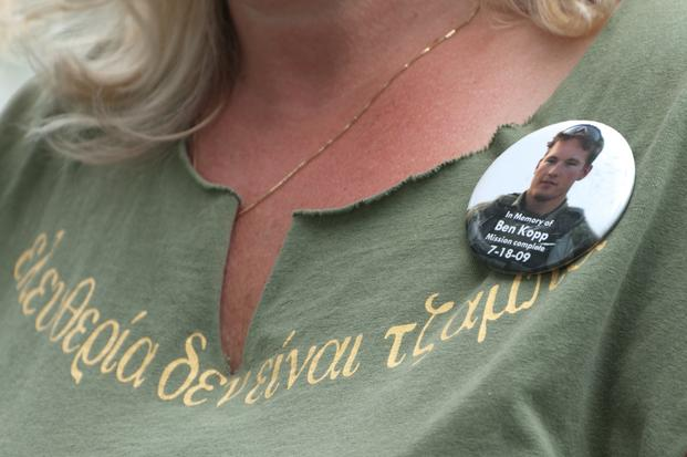 Jill Stephenson, mother of U.S. Army Cpl. Benjamin S. Kopp, who passed away July 10, 2009, after complications from a gunshot wound, wears a button in remembrance of her son on Memorial Day, May 27, 2013, at Section 60 of Arlington National Cemetery in Arlington, Va. (Laura Buchta/U.S. Army)