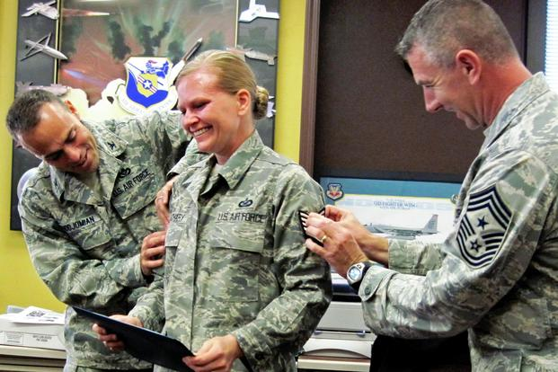 Newly promoted Tech. Sgt. Stacia Zachary, Team Eglin Public Affairs, receives her stripes from Col. Sal Nodjomian, 96th Air Base Wing commander, and Chief Master Sgt. Tom Westermeyer, 96th command chief Nov. 9, 2010. (U.S. Air Force/Chrissy Cuttita)