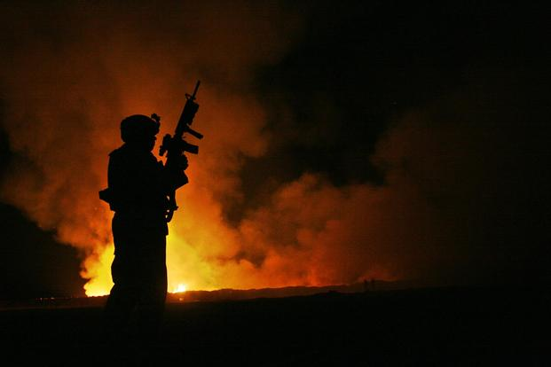 A soldier watches over the civilian fire fighters at the burn pit as smoke and flames rise into the night sky behind him at Camp Fallujah, Iraq on May 25th, 2007. (U.S. Marine Corps/Cpl. Samuel D. Corum)
