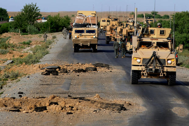 U.S. Army members with 782nd Alpha Company make their way around gigantic improvised explosive device blast holes that were created just a few hours prior to their convoy passing through April 30, 2010, Southern Afghanistan. (Photo: U.S. Army)