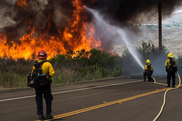 Firefighters with the Camp Pendleton Fire Department combat a fire in the Santa Margarita/De Luz Housing area on Marine Corps Base Camp Pendleton, California, July 6, 2018. (Dylan Chagnon/Marine Corps)