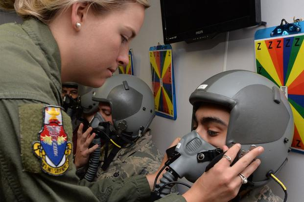 U.S. Air Force Senior Airman Darrian Caskey performs a seal check on the mask of 1st Lt. Alex Medina in the altitude hypobaric chamber for USAFSAM hypoxia demo training at Wright-Patterson Air Force Base, Ohio, April 26, 2017 (U.S. Air Force/Michelle Gigante)