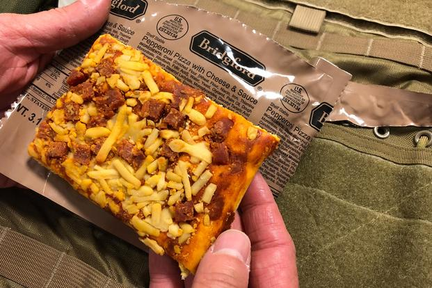 Staff writer Matthew Cox inspects and taste-tests the new MRE pizza, sent to Military.com by the Army's Combat Feeding Directorate in Natick, Massachusetts. (Military.com/Hope Hodge Seck)