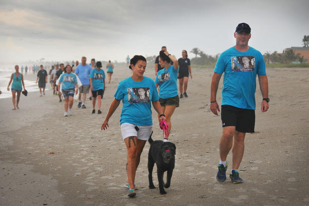 Air Force veteran Stacey Pavenski, left, 46, of Palm Bay, Florida, walks on the beach with her therapy dog, Memphis Bellw during a 3K she organized. (Photo courtesy of Florida Today via DVIDS)