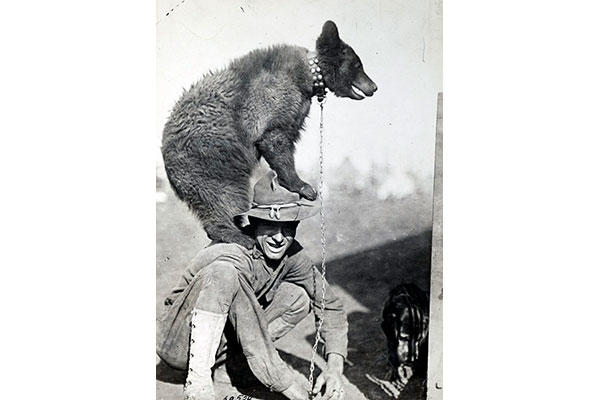 A World War I soldier lets the regimental mascot climb on him. (Photo: National Archives and Records Administration)