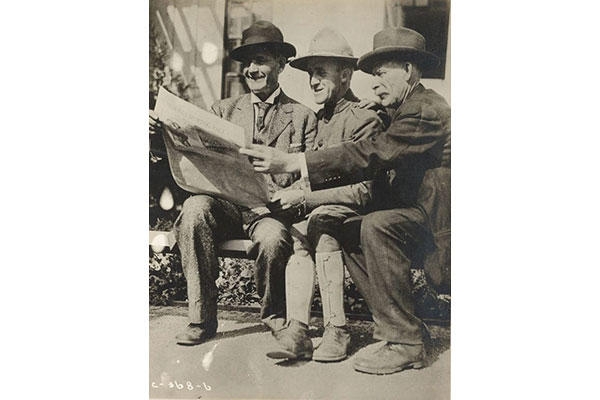 A father, son, and uncle share a newspaper on a visitor's day during training camp. (Photo: National Archives and Records Administration)