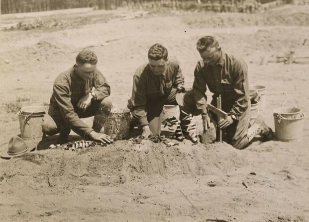 Soldiers in a training camp at Plattsburg, New York, show off the grave they created for a dummy of the German kaiser during training on trench construction. (Photo: National Archives and Records Administration)