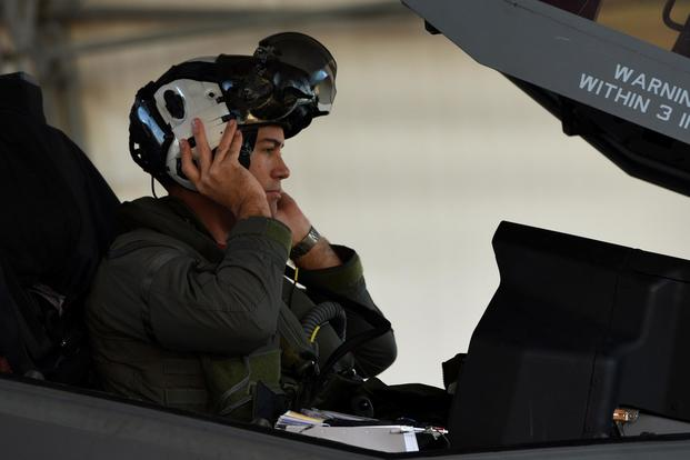 U.S. Navy Lt. Cmdr. Charles Escher, Strike Fighter Squadron (VFA-101) operations officer, dons his helmet prior to flying an Air Force F-35A Dec. 6, 2016, at Eglin Air Force Base, Florida. (U.S. Air Force/ Staff Sgt. Peter Thompson)