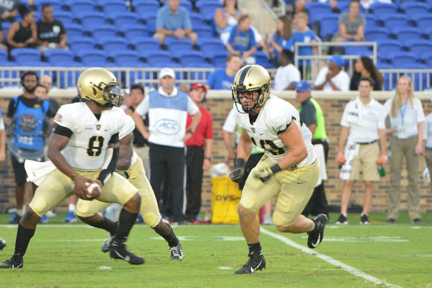 Cadet Kelvin Hopkins Jr., Army quarterback, fakes a handoff to running back Andy Davidson during the season-opening game against Duke University. (U.S. Army photo by Sgt. Brian Stephenson)