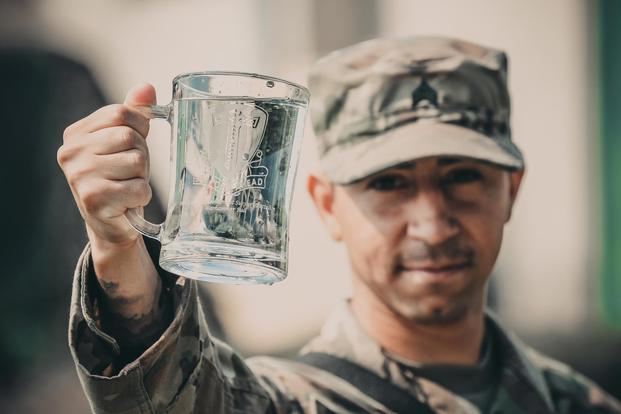 Sgt. Daniel Baudoin, a water purification specialist with the 240th Composite Supply Company of Baumholder, Germany, proudly displays his battalion crest June 2, 2018 which contains freshly purified water he and his team produced. (Michigan Army National Guard/Spc. Aaron Good)
