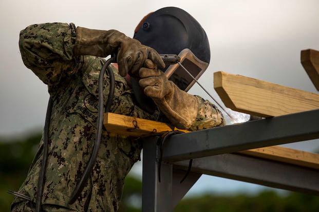 A Seabee welds metal for the Medal of Honor Hospital Corpsman 3rd Class Bush Battle Aid Station for the Correctional Custody Unit 2.0 program March 28 aboard Camp Hansen, Okinawa, Japan. (U.S. Marine Corps/Cpl. Tayler P. Schwamb)