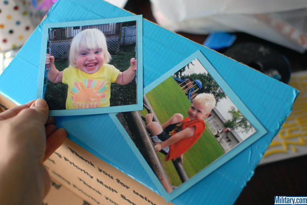 Place your photos on your Tape photos to your paper for your military birthday care package box. (Military.com)