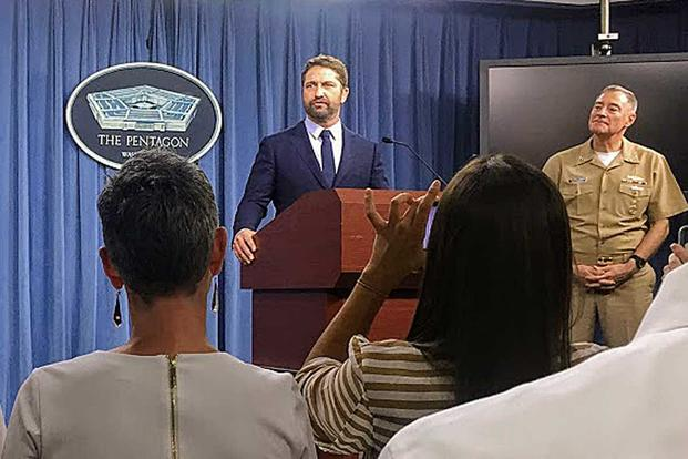 "Actor Gerard Butler speaks to reporters at the Pentagon on Oct. 15, 2018, promoting his new movie, ""Hunter Killer."" Navy Vice Adm. Fritz Roegge stands to his right. Photo by Oriana Pawlyk/Military.com"