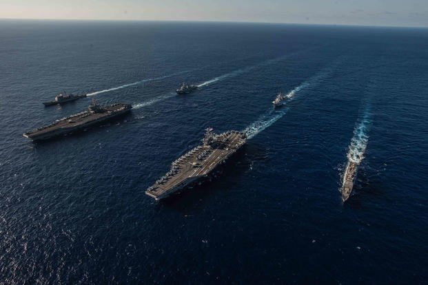 The aircraft carriers USS Ronald Reagan (CVN 76), left, and USS John C. Stennis (CVN 74) lead ships of their respective carrier strike groups as they transit the Philippine Sea during dual carrier operations, Nov. 16, 2018. (U.S. Navy photo/Kaila V. Peters)