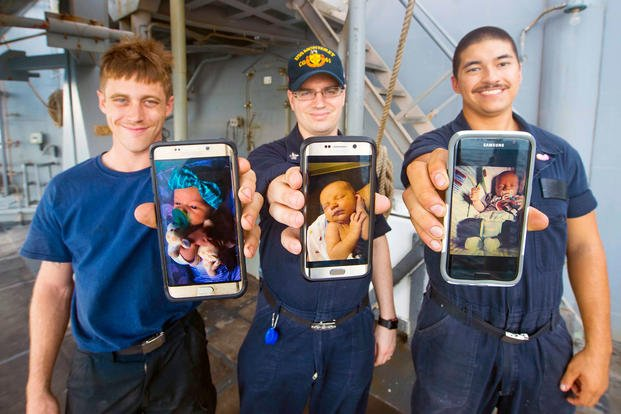 Seaman Cody Slone, left, Petty Officer 1st Class Joshua Morcom and Seaman Chase Marr, show imagery of their newborn babies from their cell phones aboard the guided-missile cruiser USS Monterey (CG 61).  (U.S. Navy/William Jenkins)