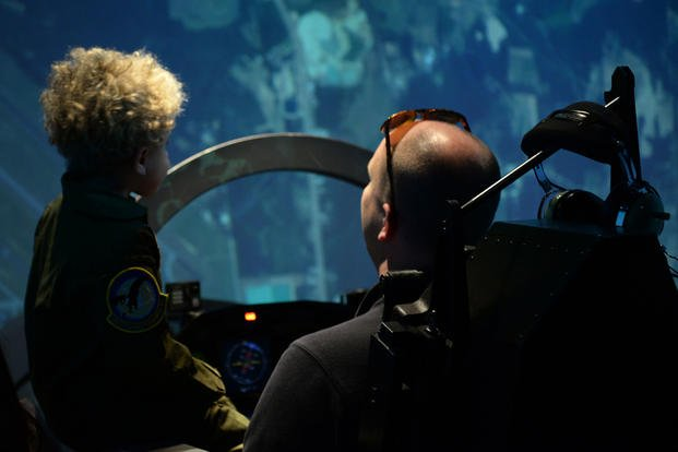Tobias Taylor, Pilot for a Day, and Clay Taylor, Tobias' father, try out a T-6 simulator at the 14th Operations Group, Dec. 6, 2018, on Columbus Air Force Base, Mississippi.  (U.S. Air Force/Hannah Bean)