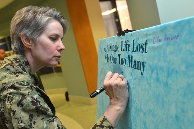 Lt. Cmdr. Karen Downer writes a name on a Suicide Awareness Memorial Canvas in honor of Suicide Awareness Month at Naval Hospital Jacksonville, Sept. 10, 2018. (U.S. Navy/Jacob Sippel, Naval Hospital Jacksonville).