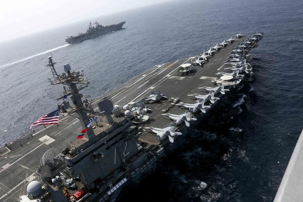 The USS Abraham Lincoln and the Assault Ship USS Kearsarge sail alongside as the Abraham Lincoln Carrier Strike Group and Kearsarge Amphibious Ready Group conduct operations in the U.S. 5th Fleet area of operations. (U.S. Navy/Mass Communication Specialist 1st Class Brian M. Wilbur)