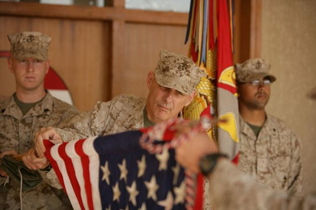 Maj. Gen. John F. Kelly, commanding general, Multi National Force-West, cases the colors signifying the transfer of MNF-West's headquarters to Al Asad Air Base. Kelly has ordered Camp Fallujah to close and handed back to the Iraqis in the next few months. More than 8,000 Marines from the camp have been relocated throughout the Anbar province or sent home. (Lindsay Sayres/U.S. Marine Corps)