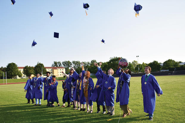 High school graduates toss caps.