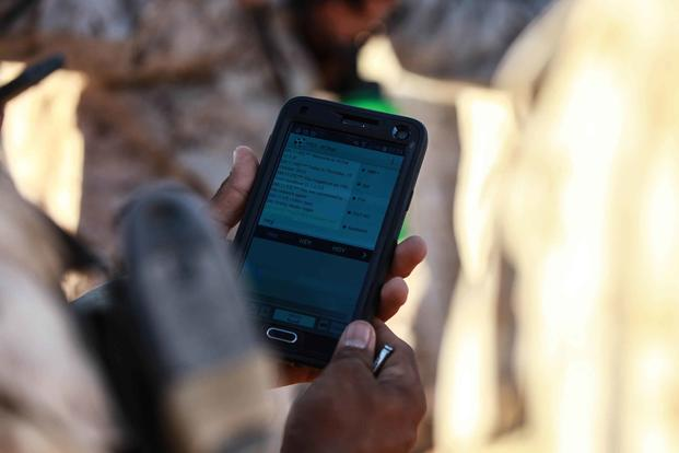 A Marine uses a cellphone in the field in 2016. (U.S. Marine Corps Photo by Lance Cpl. David Staten)