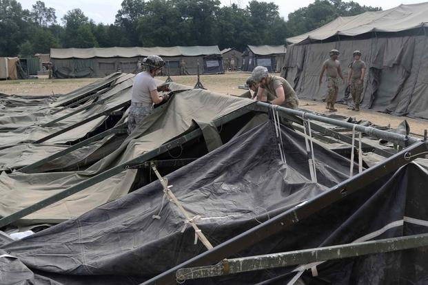 FILE PHOTO -- U.S. Army medical personnel under the 803rd Medical Center assemble a field hospital tent during the Combat Support Tactical Exercise in Fort McCoy, Wis., Aug. 12, 2019. (U.S. Army/Sgt. 1st Class Gary A. Witte, 207th Regional Support Group)